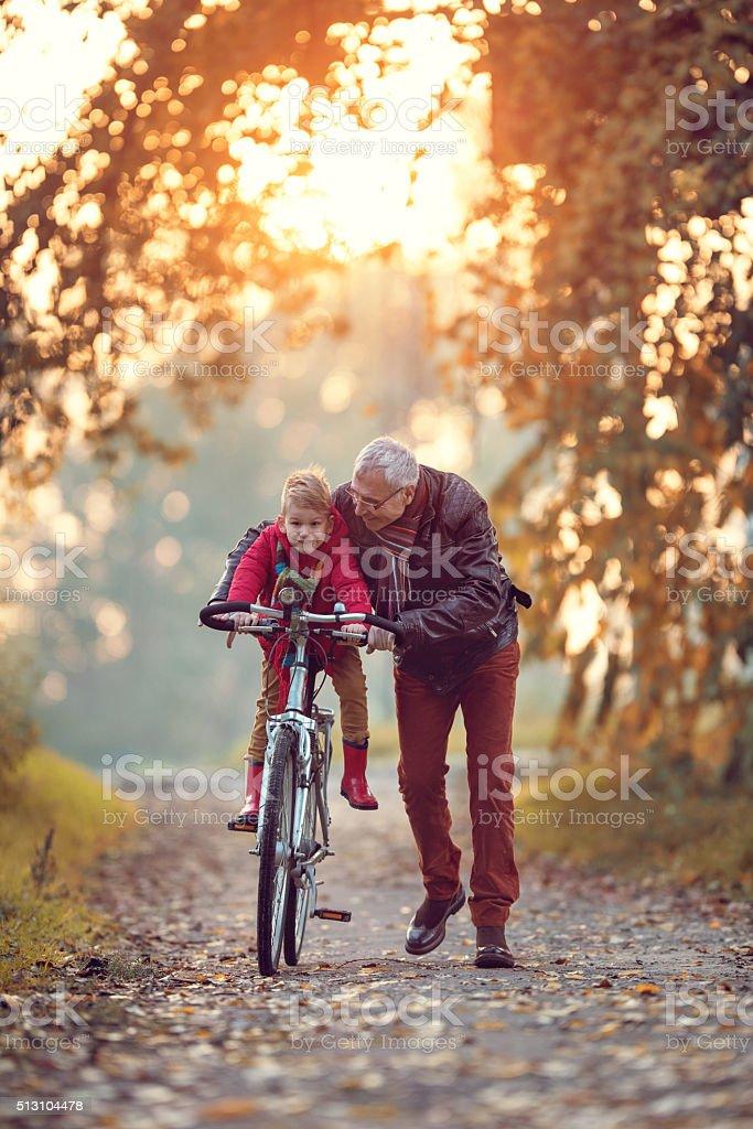 Smiling senior man teaching his grandchild how to cycle. stock photo