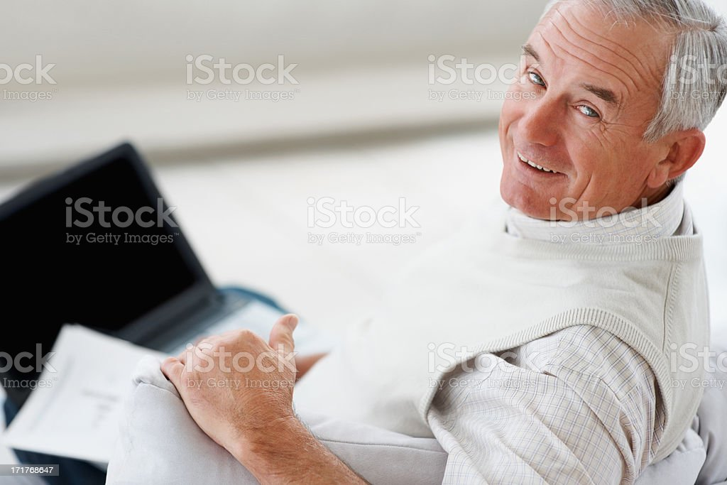 Smiling senior man using a laptop at home royalty-free stock photo