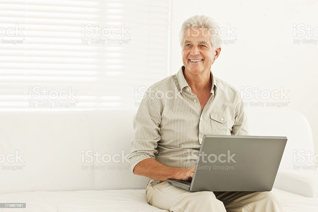 Smiling senior man using laptop at home royalty-free stock photo