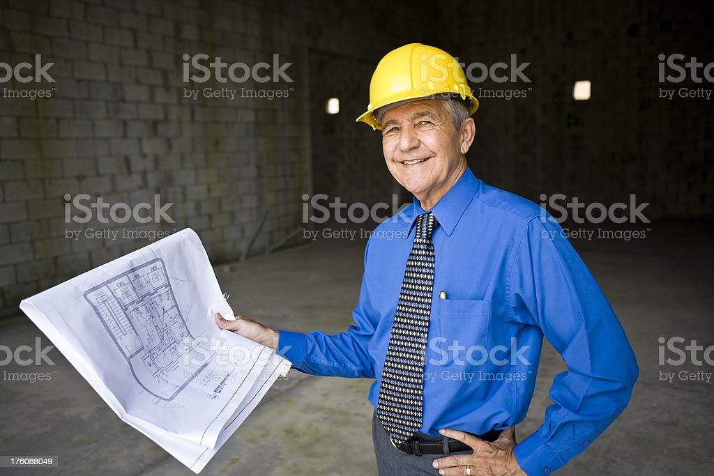 Smiling senior man wearing hardhat holding blueprints at construction site royalty-free stock photo