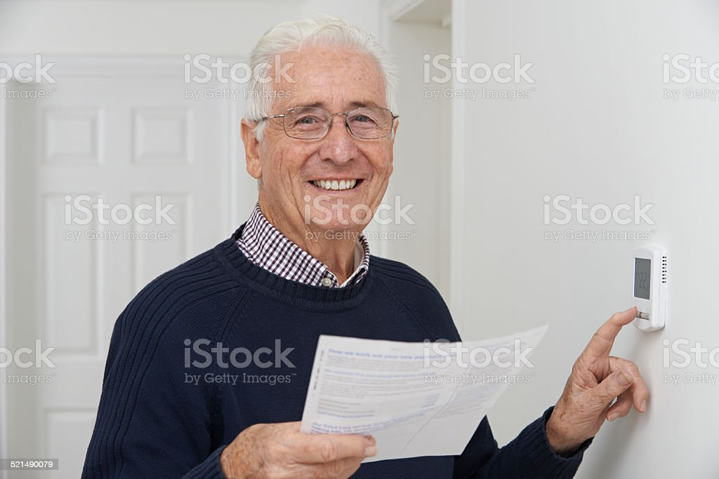 Smiling Senior Man With Bill Adjusting Central Heating Thermosta stock photo