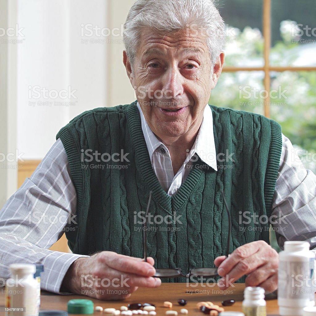 Smiling senior man with many pills royalty-free stock photo