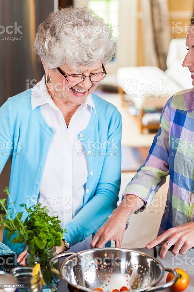 Smiling senior mother watches her daughter prepare a meal stock photo