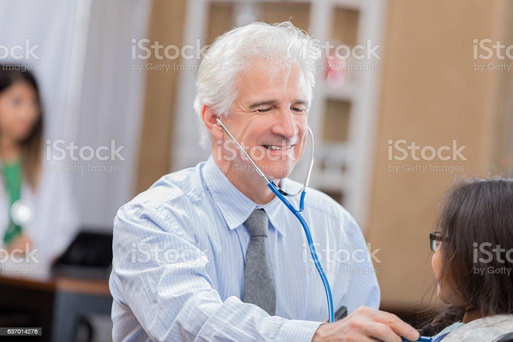 Confident senior Caucasian pediatrician uses a stethoscope to listen...
