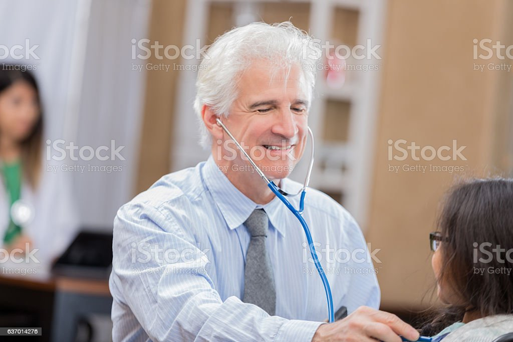 Smiling senior pediatrician examines young Asian patient during well check stock photo