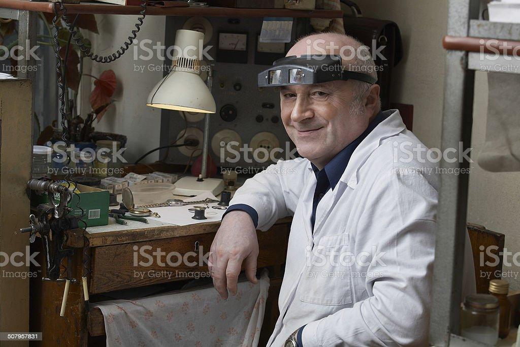 Smiling Senior Watch Repairman In Workshop stock photo