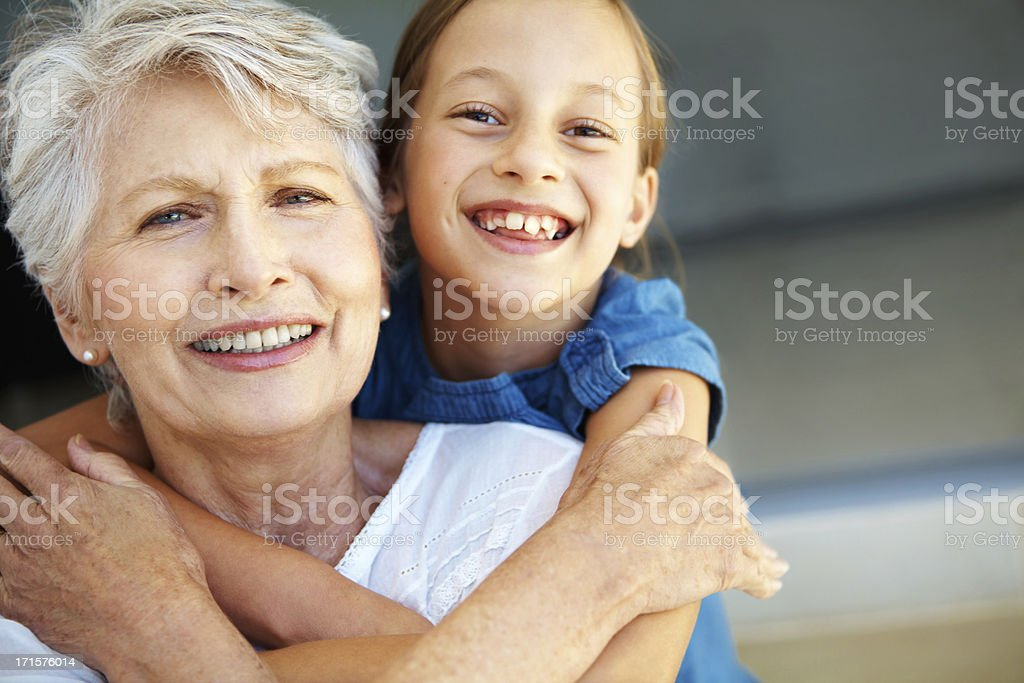 Smiling senior woman and girl embracing stock photo