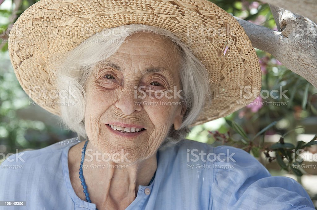 Smiling senior woman and straw hat stock photo