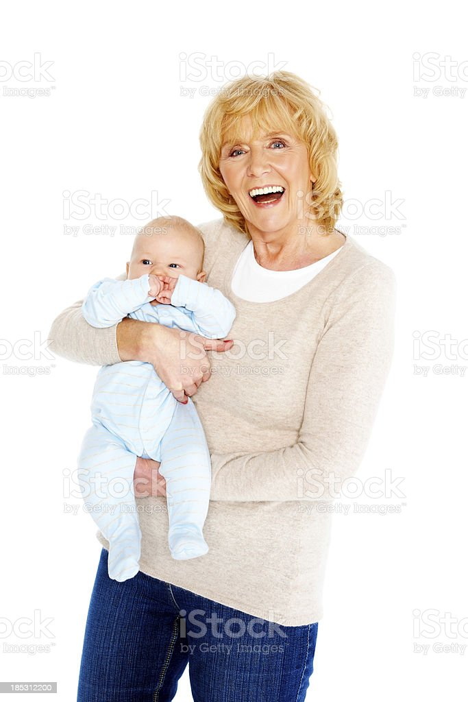 Smiling senior woman carrying her grandson royalty-free stock photo