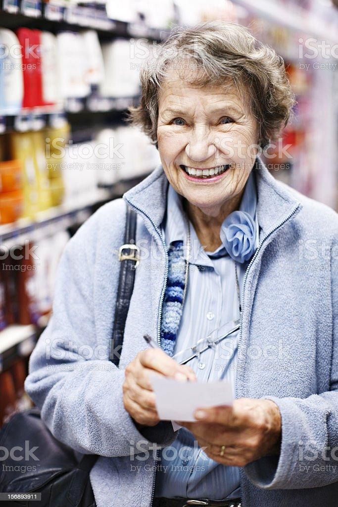 Smiling senior woman checks her shopping list in supermarket royalty-free stock photo