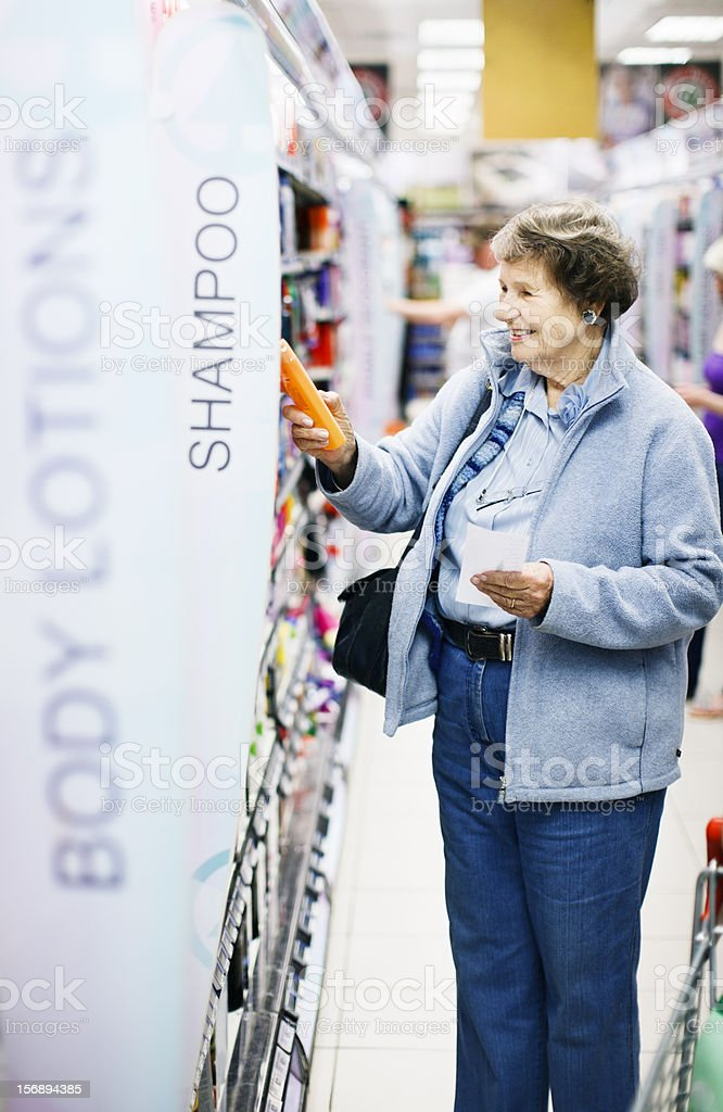 Smiling senior woman chooses shampoo in supermarket stock photo