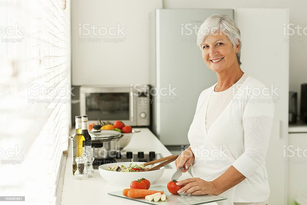 Smiling senior woman cutting vegetables in kitchen royalty-free stock photo