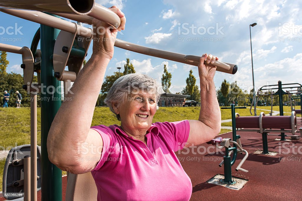 Smiling senior woman doing strength exercises at outdoor gym. stock photo