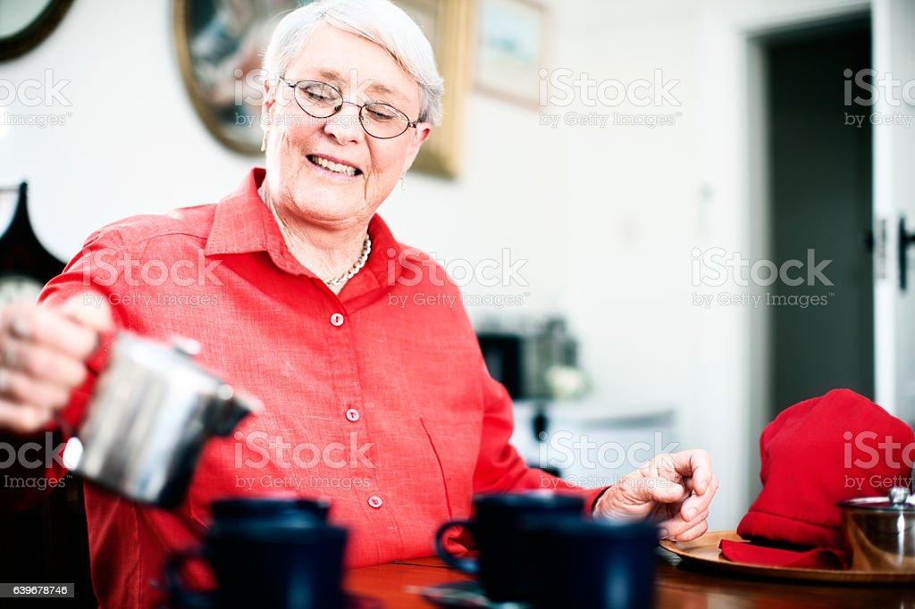 Smiling senior woman entertaining at her home stock photo