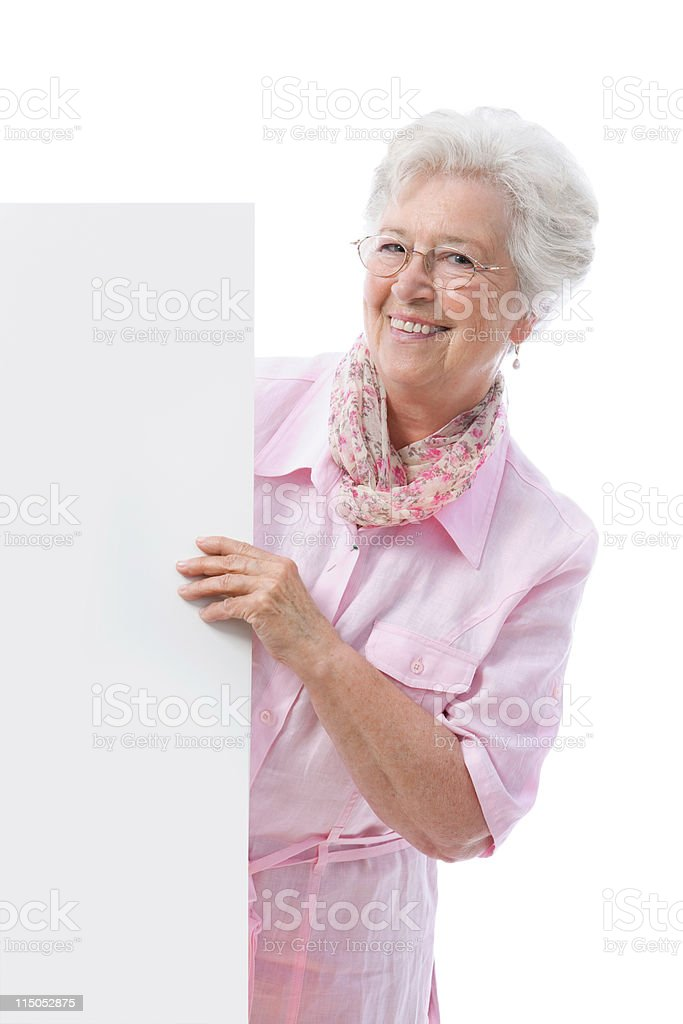 Smiling senior woman holding up blank cardboard sign royalty-free stock photo