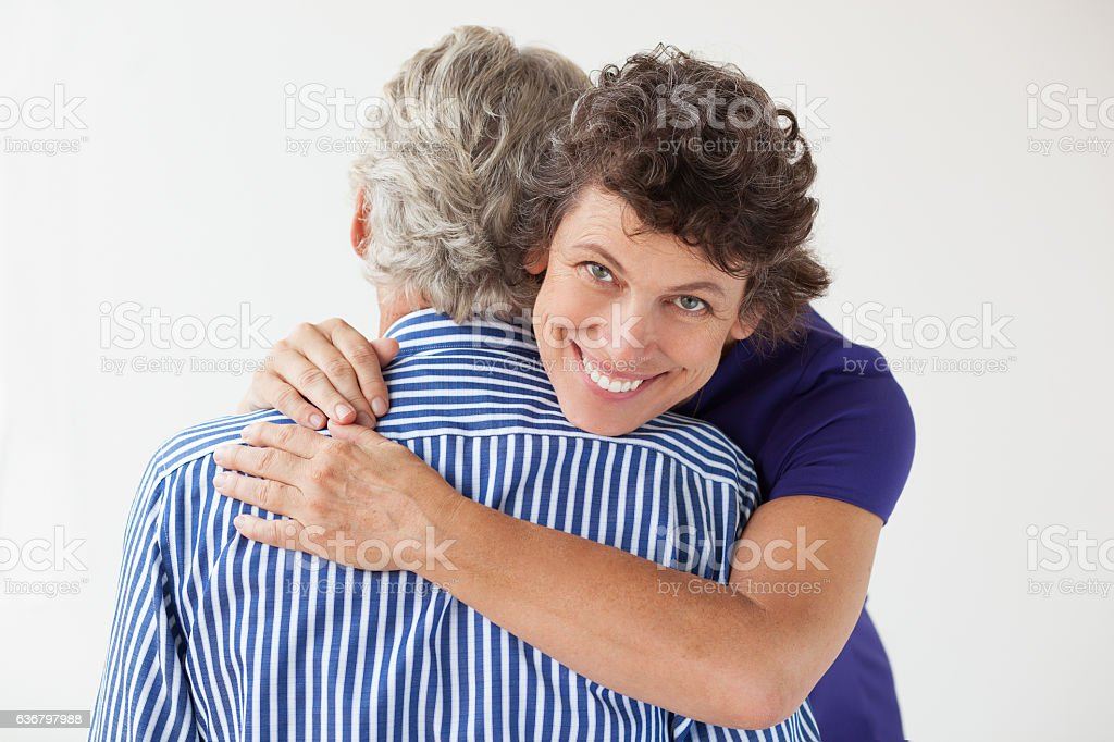 Smiling Senior Woman Hugging Husband stock photo