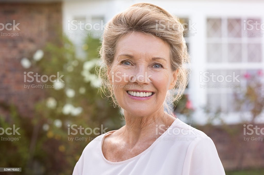 Happy senior woman standing outside her house. Content woman smiling...
