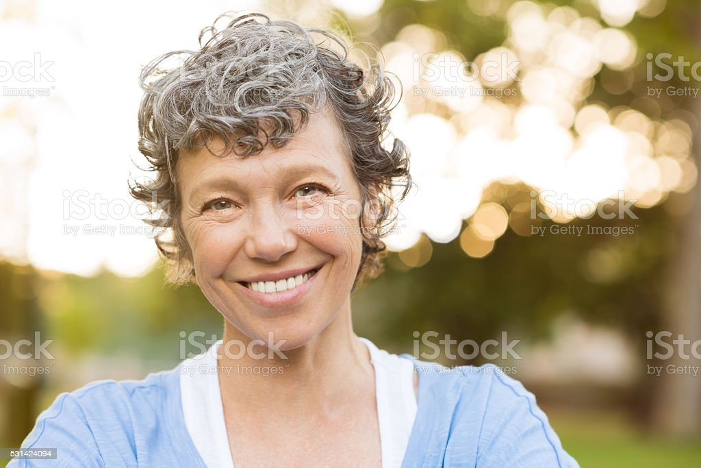 Portrait of senior woman relaxing at park. Close up face of happy...