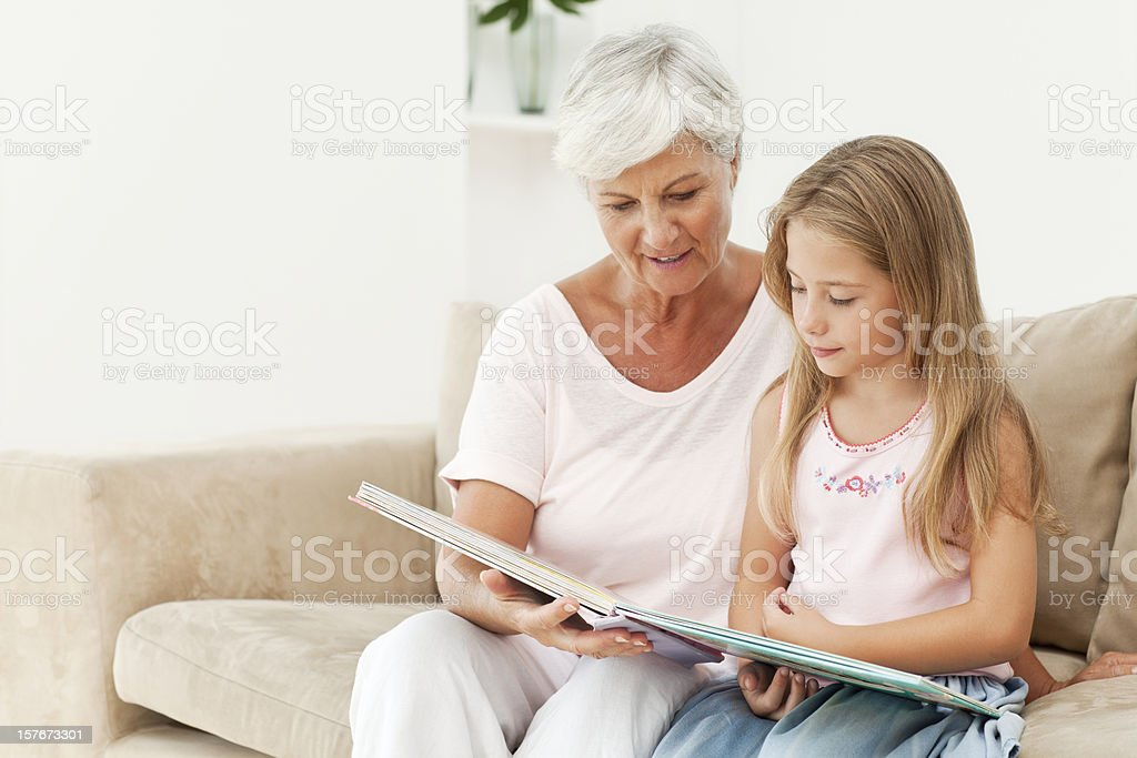 Smiling Senior Woman Reading To Young Girl royalty-free stock photo