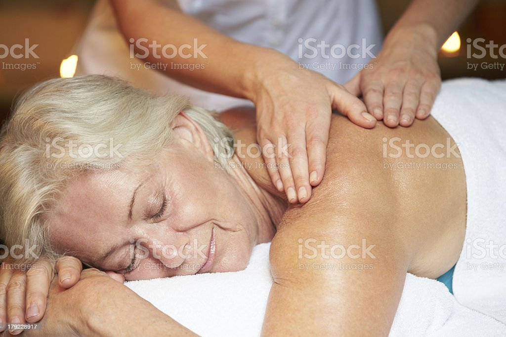 Smiling senior woman receiving a massage at the spa stock photo