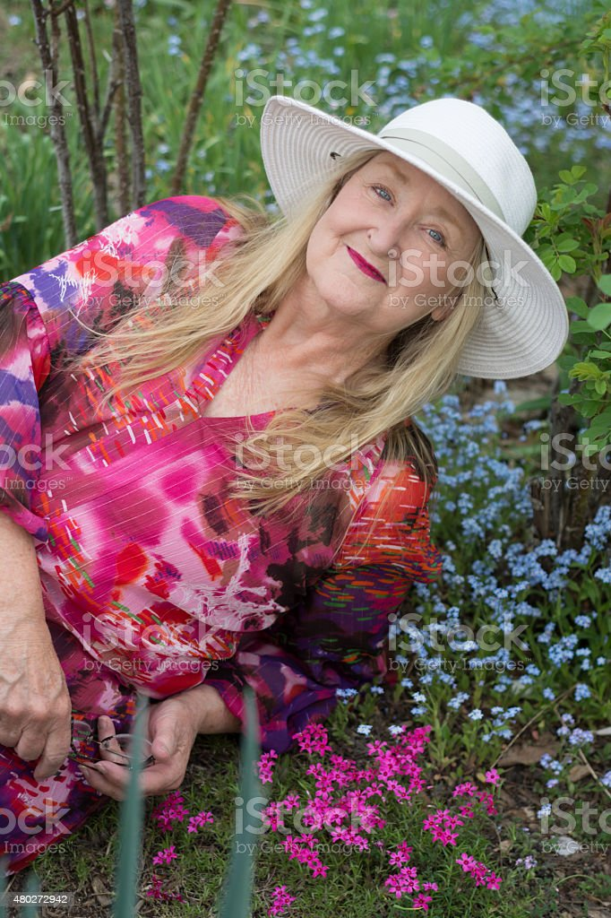 Smiling senior woman reclining in spring garden, waist up. stock photo