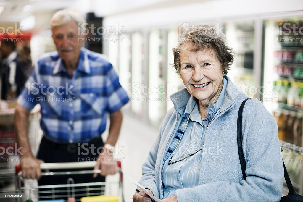 Smiling senior woman shopper in supermarket aisle, husband behind her stock photo
