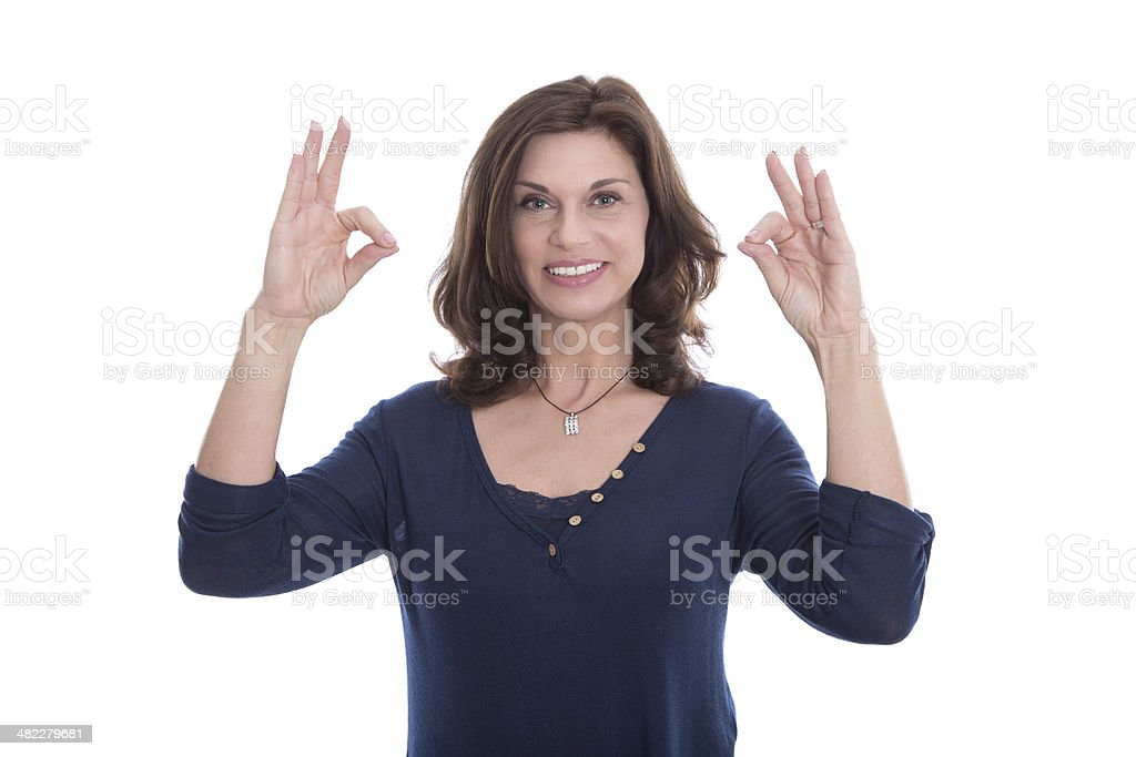 Smiling senior woman showing sign excellent with her fingers. stock photo