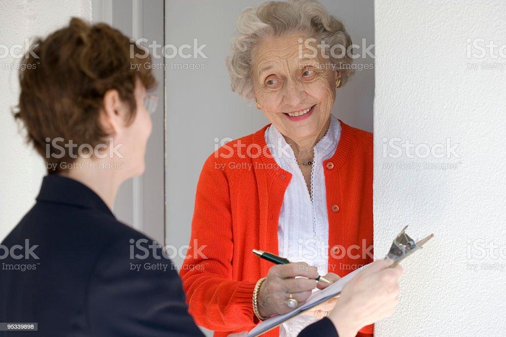 Smiling senior woman signing petetion stock photo