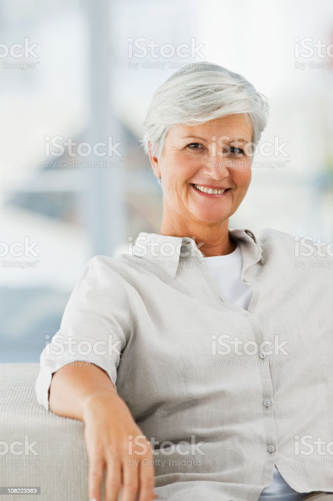 Smiling senior woman sitting on couch royalty-free stock photo