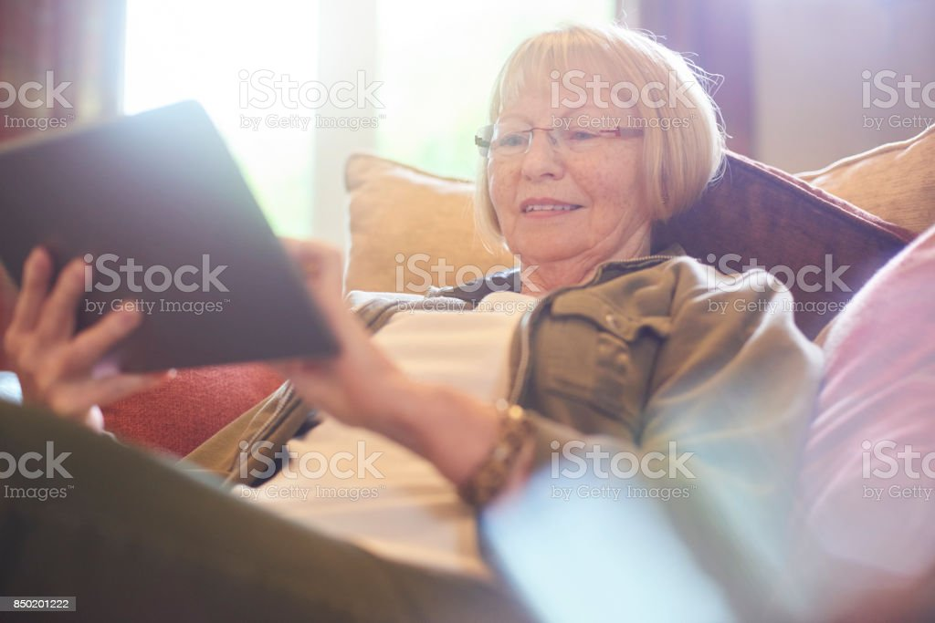 smiling senior woman surfing the net stock photo