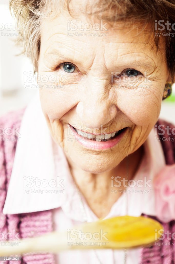 Smiling senior woman tasting something from a wooden spoon stock photo