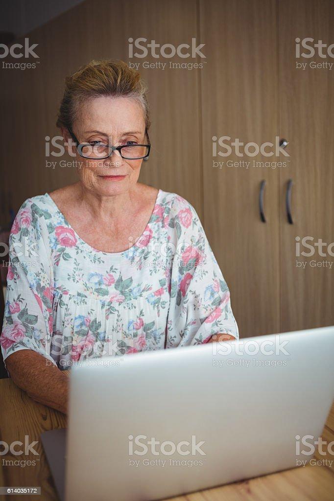 Smiling senior woman using a laptop stock photo