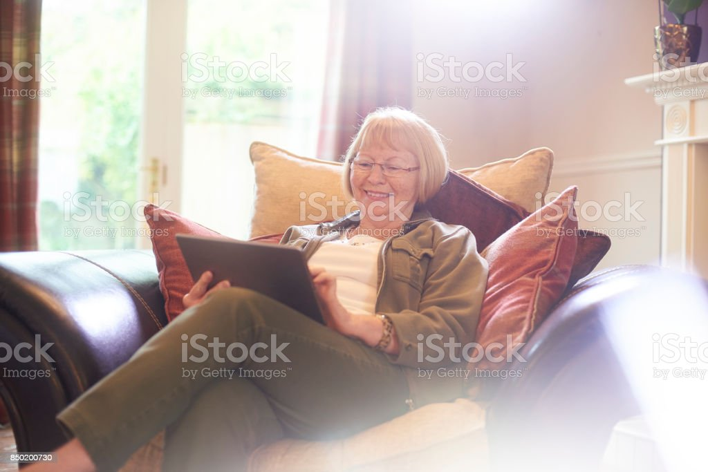smiling senior woman using digital tablet stock photo