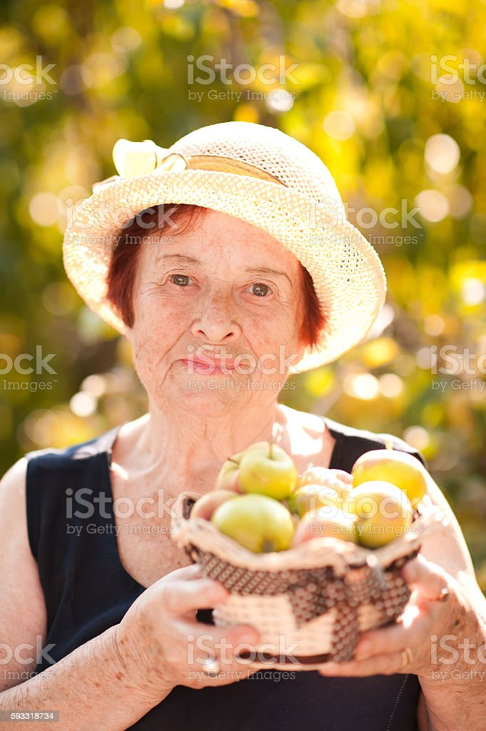 Smiling senior woman with apples stock photo