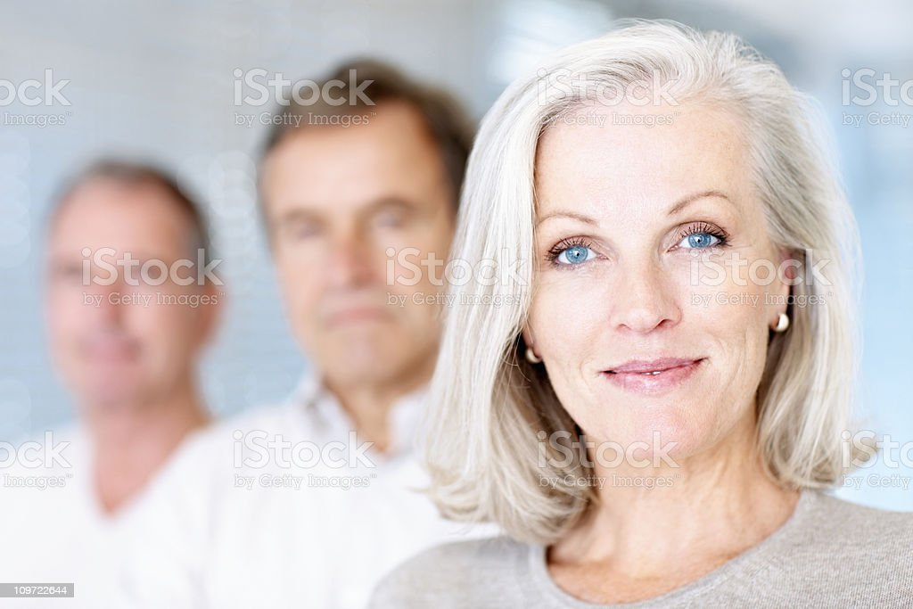 Smiling senior woman with men at the background stock photo
