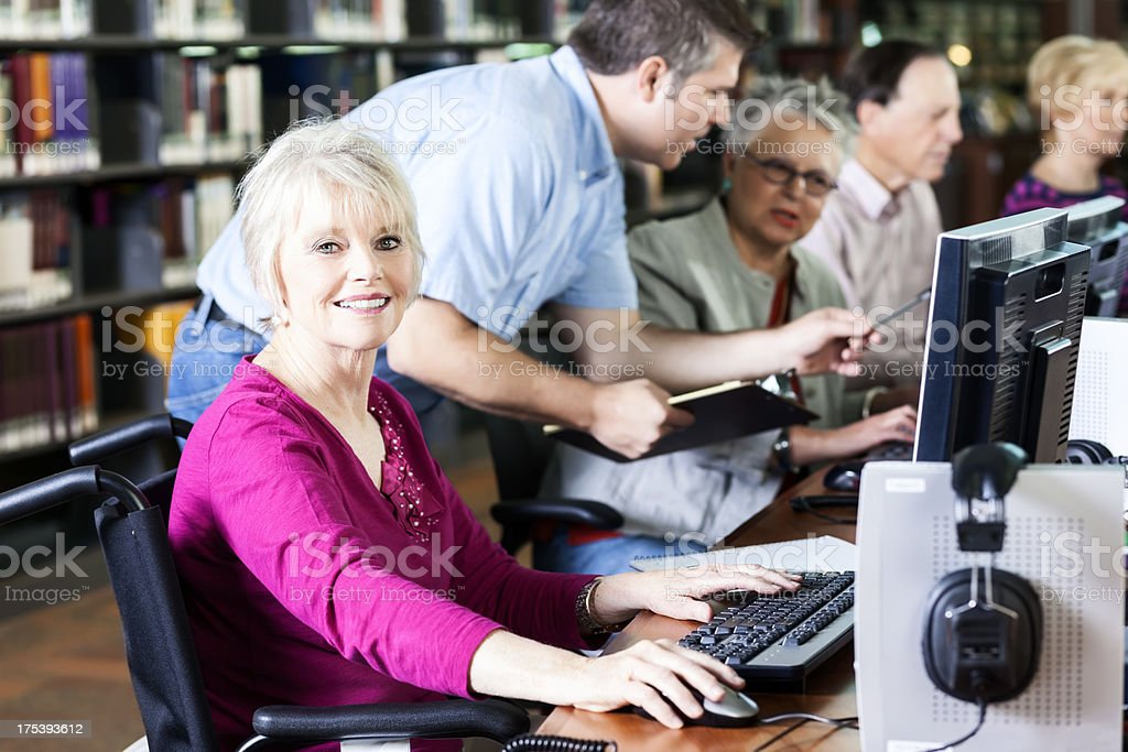 Smiling Senior Woman with Wheelchair at Computer in Library royalty-free stock photo