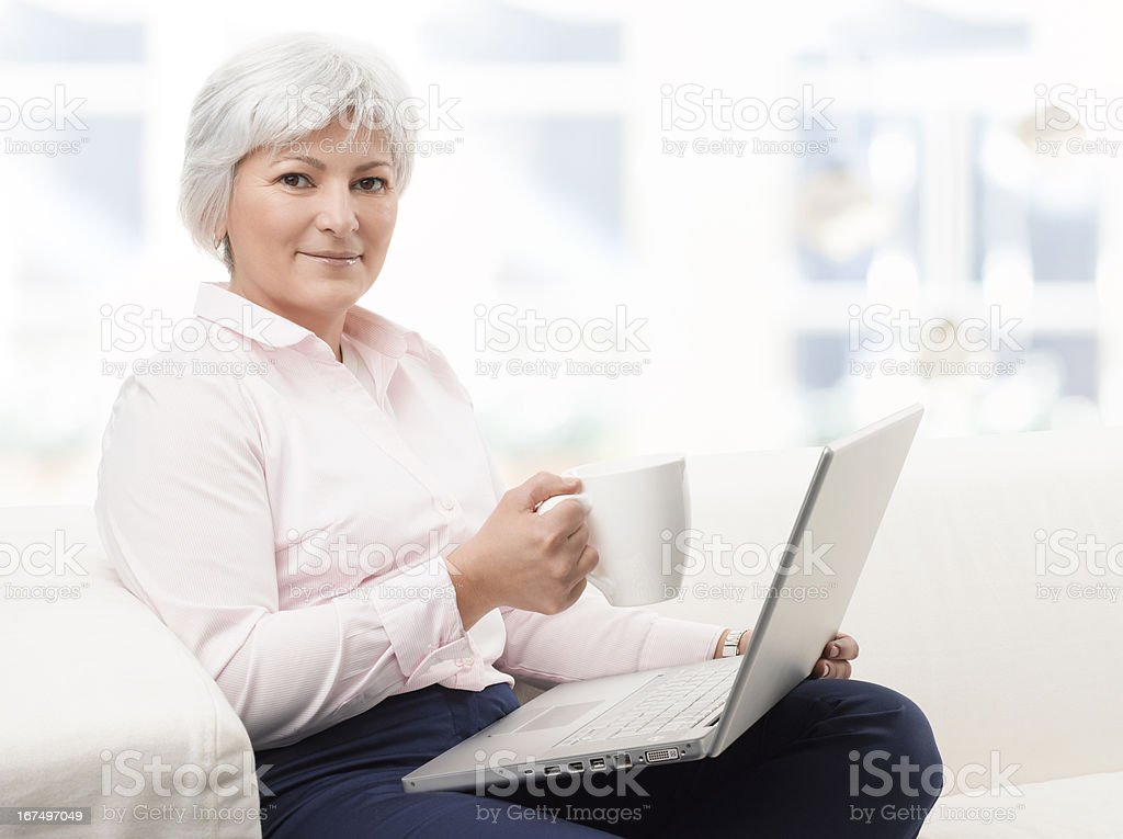 Smiling senior woman working on laptop royalty-free stock photo