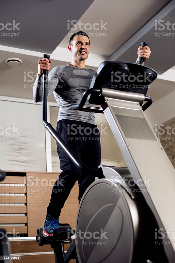 Smiling sexy muscle man doing cardio training stock photo