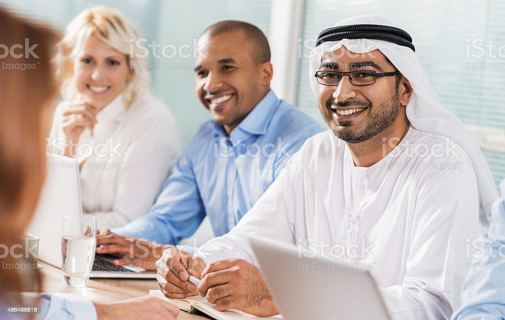 Smiling sheik with business people on a meeting. stock photo