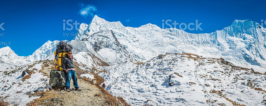 Smiling Sherpa porter with expedition kit resting Himalaya mountains Nepal stock photo