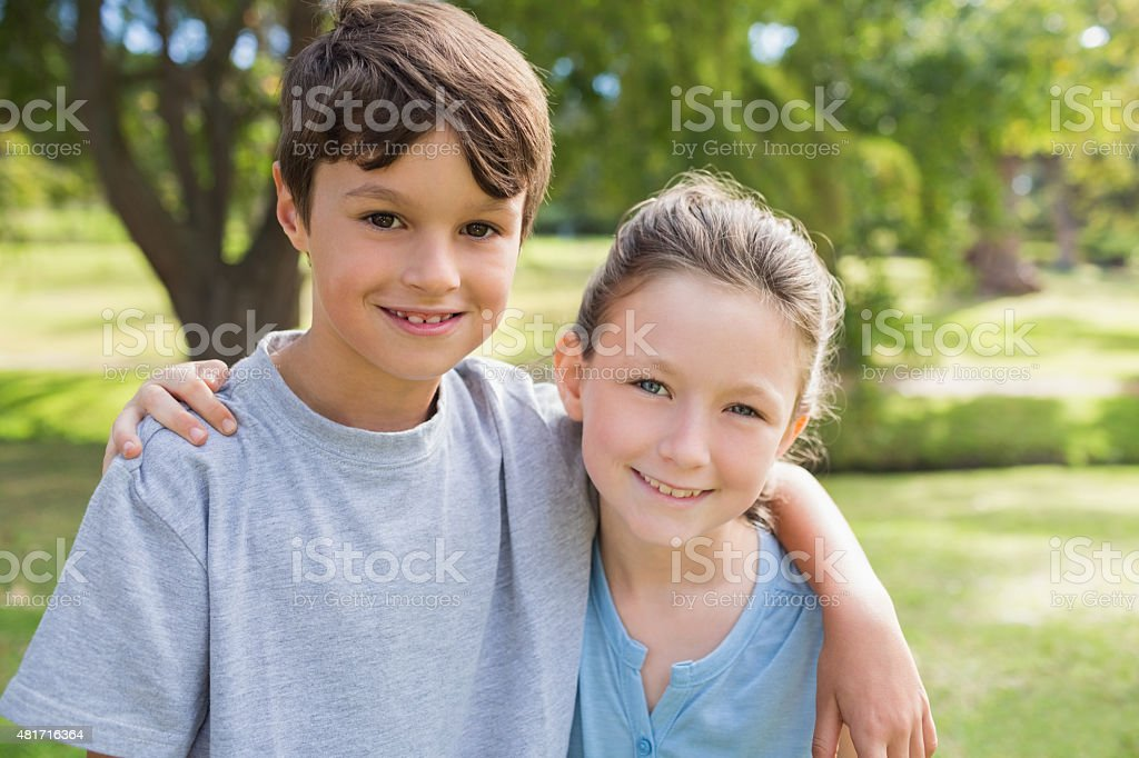 Smiling sibling looking at camera in the park stock photo