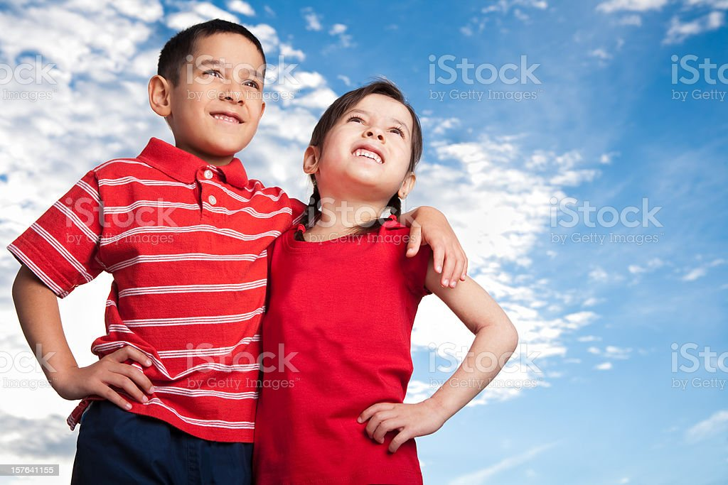 Smiling sibling standing against blue sky royalty-free stock photo