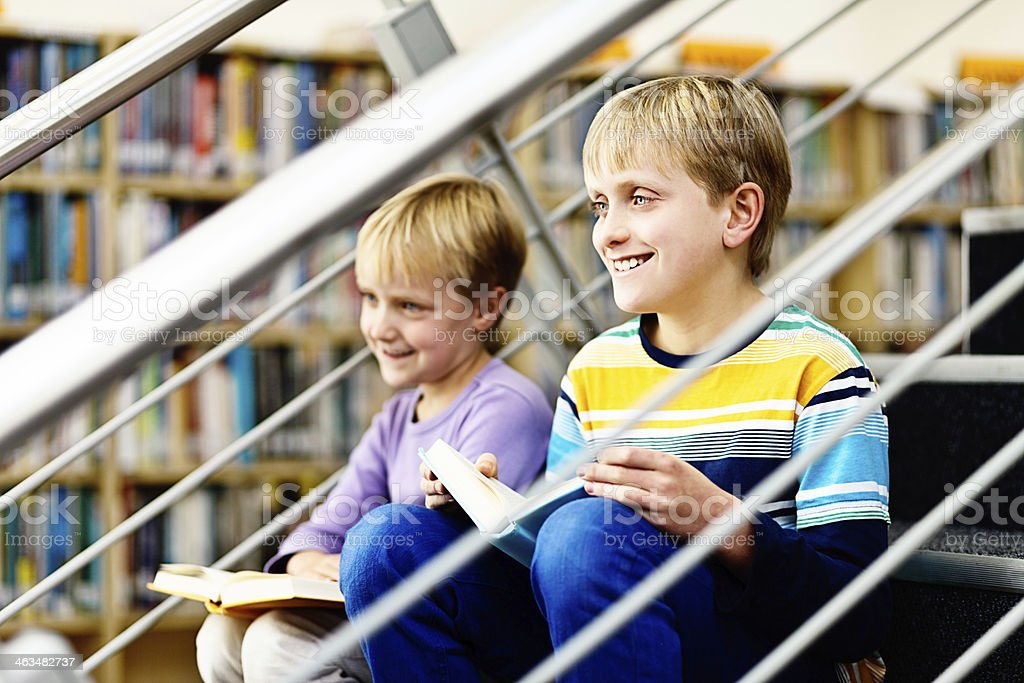Smiling siblings sit on library steps with their books royalty-free stock photo