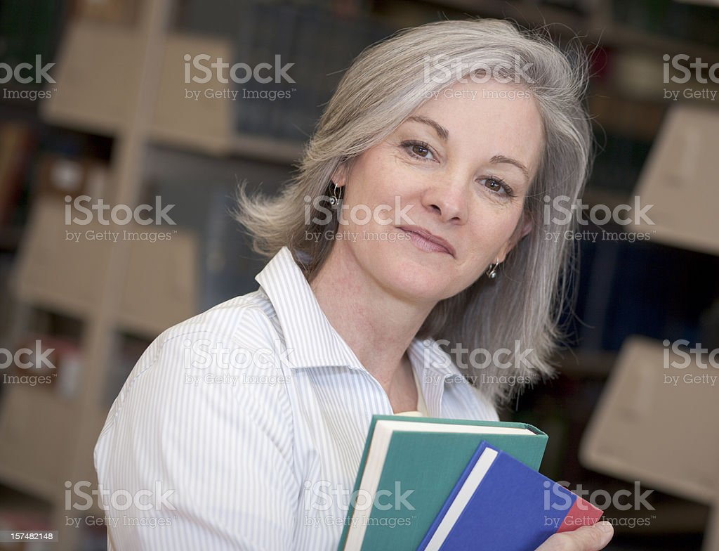 Smiling silver-haired woman holding books in a library royalty-free stock photo