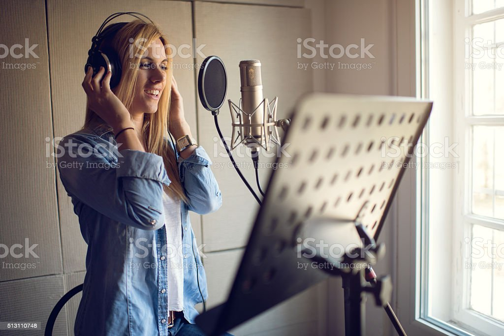 Smiling singer recording in music studio. stock photo