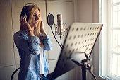 Smiling singer recording in music studio.