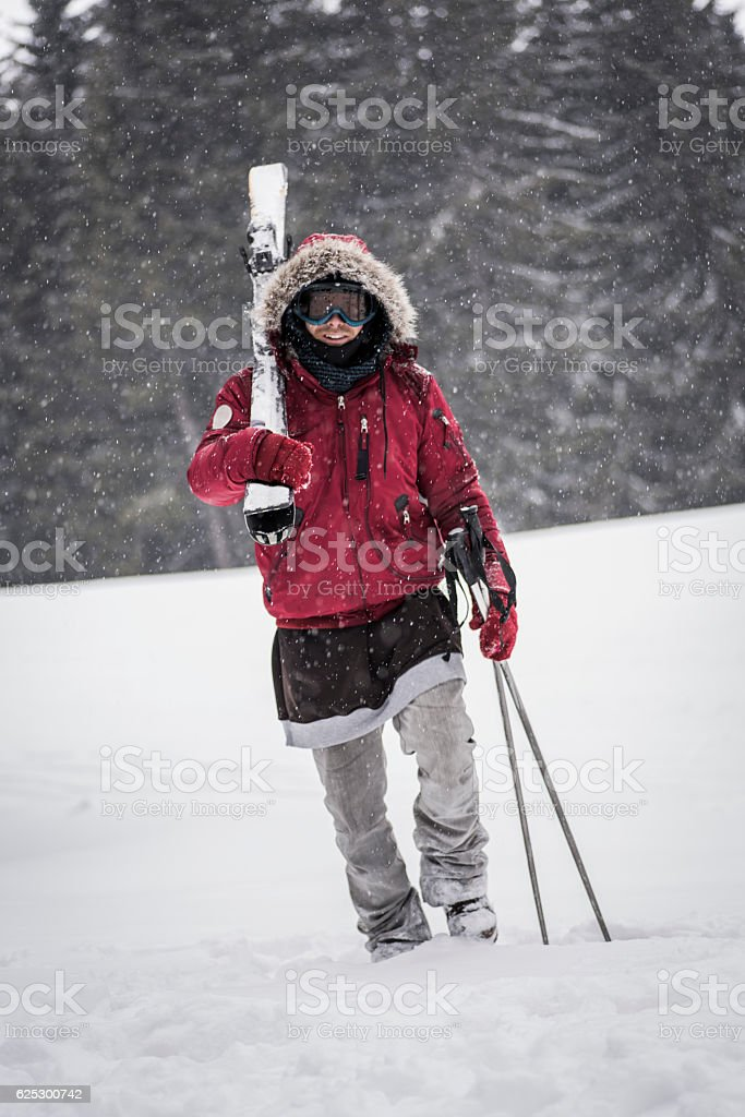 Smiling skier carrying skis stock photo