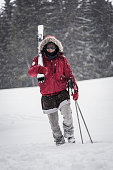 Smiling skier carrying skis
