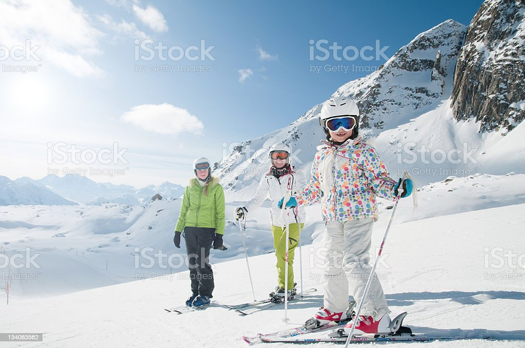 Smiling skiers on a snowy mountain under a beautiful sky stock photo
