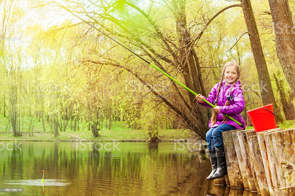 Smiling small girl fishing near beautiful pond stock photo